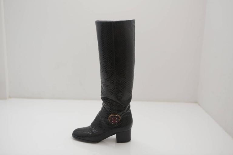 """Chanel pair of black snakeskin boots with 15"""" zipper less shaft, 2"""" heel and ruby colored stone & pearl adornment."""