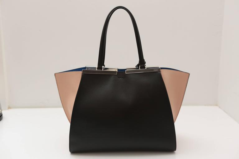 Black and nude leather exterior with blue micro suede interior featuring a tab snap top closure and jut-out sides to create extra space.  Polished silver hardware completes this must-have classic from the House of Fendi.