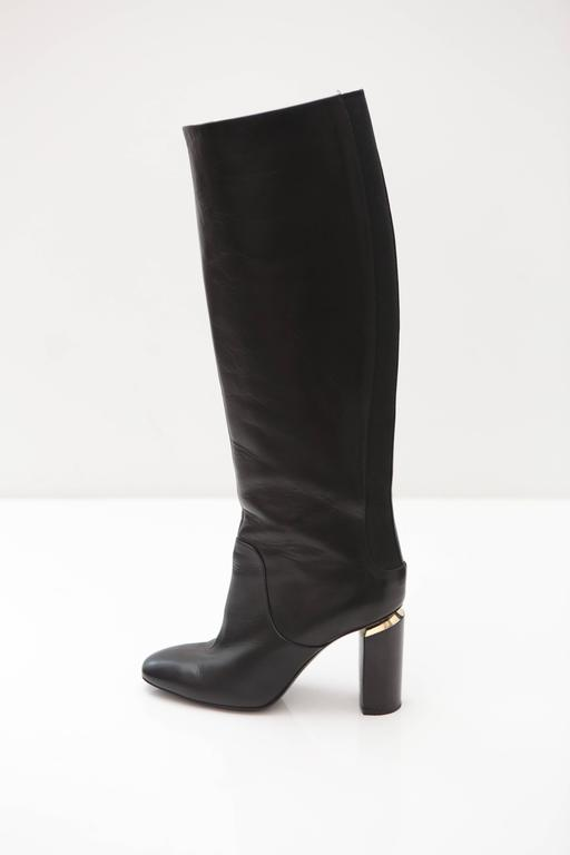 Knee high slip on boot with elastic back and silver piping along the sole. Heel features mirrored effect and stacked wooded detail. Note, the shaft of the boot is a slip on and has no zipper or closure hardware.