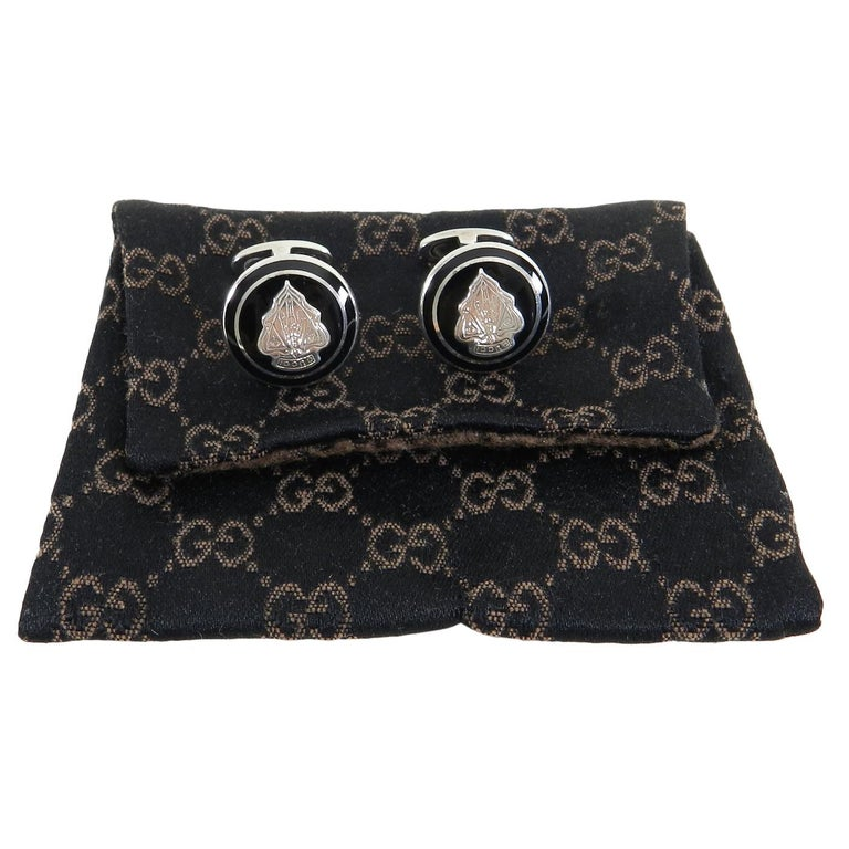 Gucci Sterling Silver Black Enamel Crest Cufflinks.  Round design with Gucci logo crest and black enamel. Fully hallmarked for 925 sterling silver.  Includes pouch.  Measures 0.75