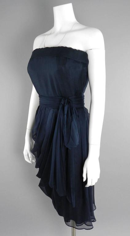 """YSL Yves Saint Laurent vintage Haute Couture numbered dress circa 1980's. Black sheer silk chiffon with matching belt. Strapless design, zipper at side. Excellent vintage condition with no flaws to note. Garment designed to fit 36"""" bust person, 26"""