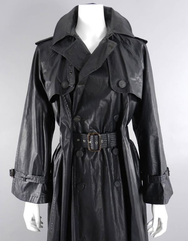 Vintage circa 1990's Jean Paul Gaultier waxed canvas trench coat. Belt weaves through slits / belt-holes in jacket. There are small tears / old repairs on 3 out of 5 of the belt holes. The most damaged one is pictured. Does not detract when worn.