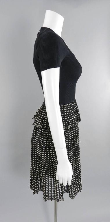 "Alexander McQueen black ribbed stretch knit dress with black and white eyelet skirt.  New with tags.  Stretchy pullover design with no zippers or closures.  Tagged size M (approx. size USA 6/8). To fit 34-35"" bust, 27-29"" waist, semi full"