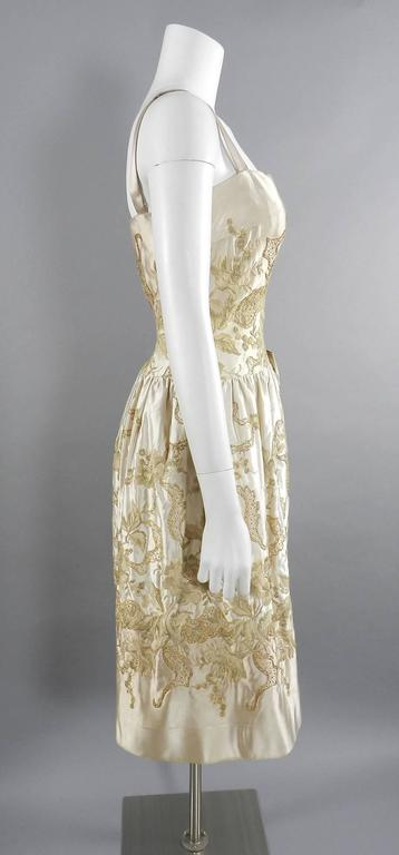 Vintage 1950's Florilege Balmain Ivory Silk Embroidered Cocktail Dress.  Florilege was Balmain's ready to wear line that brought couture styling to the everyday woman. Silk satin fabric in light beige / sand and ivory with beige, taupe, and metallic