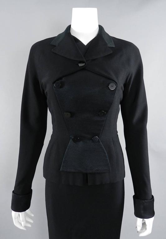 "Pierre Balmain circa early 1950's skirt suit. Black finely ribbed wool with silk satin contrast. unique fold over design at front bust, french cuffs, pencil skirt with off-centre back zipper. Skirt waist 25"", 39"" hip, 28.5"" total"