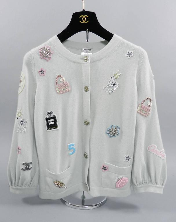 "Chanel 08P Limited Edition Lucky Charms Light Blue Cashmere Cardigan.  Decorated with brooches and patches. Size FR 36 (USA 4). Garment measures 34"" at bust unstretched at is reommended for 33/34"" bust person, shoulder to shoulder seam 13.5"", sleeve"
