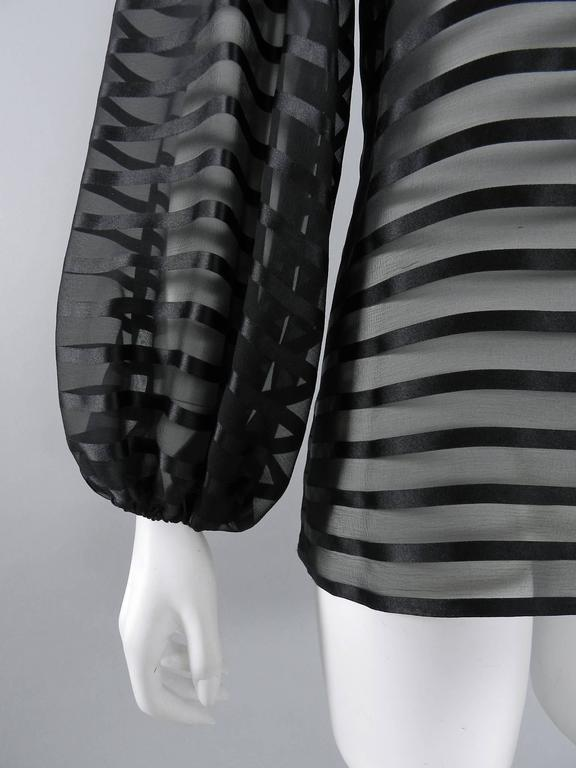 Chanel black sheer silk striped blouse.  Pull over design with no closures or zippers at neck or sides.  Straight cut body, full sleeves with elastic cuffs, CC logo at front left hip. Excellent pre-owned condition - worn once. Tagged size FR 38 (USA
