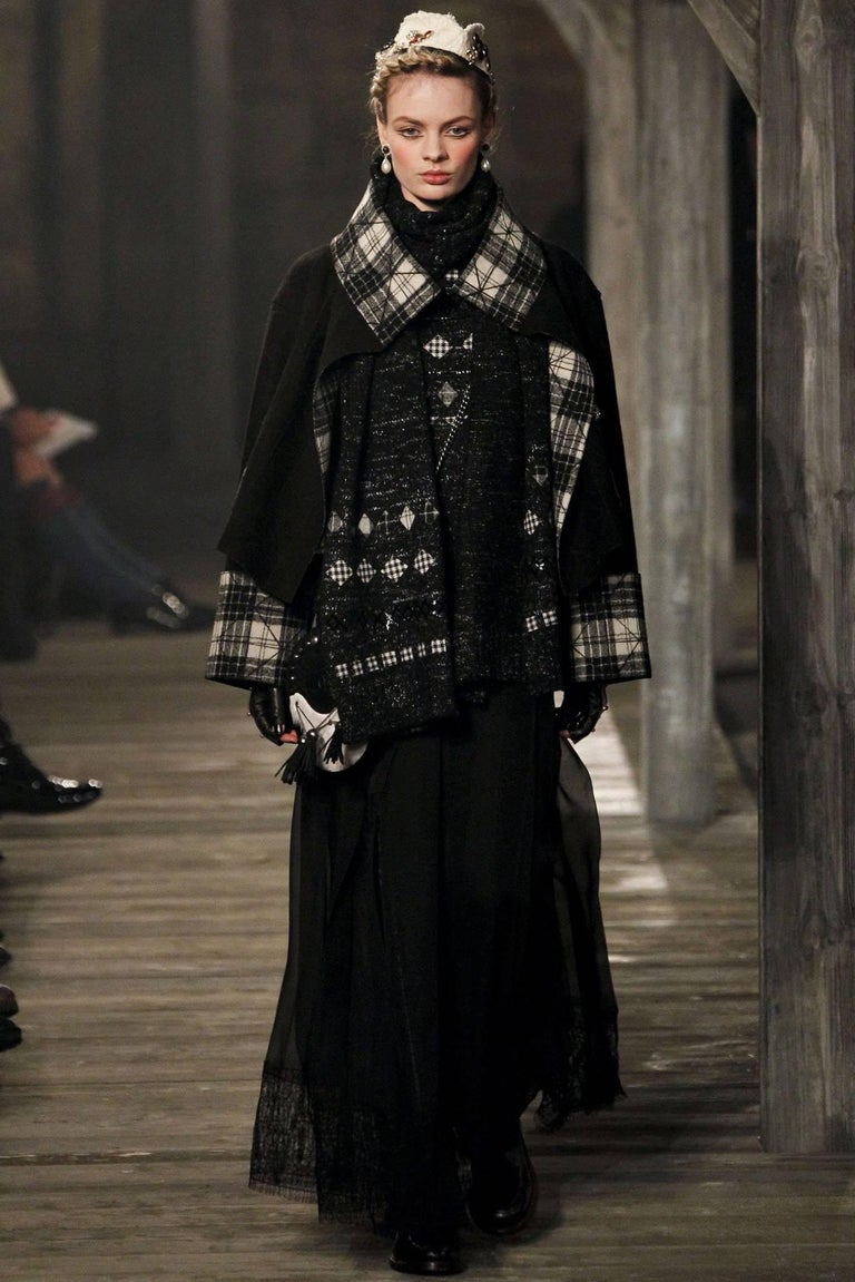 Chanel Edinburgh 13A -  2013 Runway Long Black silk kilt skirt with lace trim.  Full-length wrap design that fastens at left hip with leather straps and buckles. Garment is lined with an underskirt to knee and is semi-sheer to hem.  Underskirt is