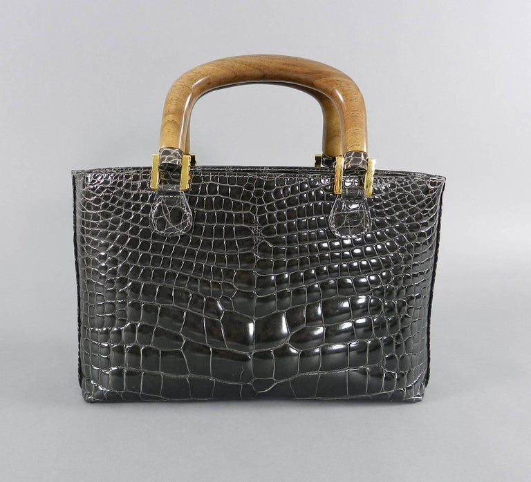 Lana Marks crocodile bag with wood handles, removable shoulder strap, and goldtone metal hardware.  Interior is lined with gray colored material. Color of bag is a dark gray with brownish tone - looks dark brown in some lighting. Measures 10 x 6.5 x