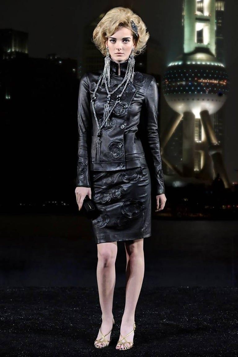 Chanel pre-fall 2010 Shanghai Paris Runway Black Camelia Leather Jacket.  High collar, fastens with gunmetal dragon buttons at left side, front hip pockets.  Tagged size FR 38 (USA 6). Garment to fit 34