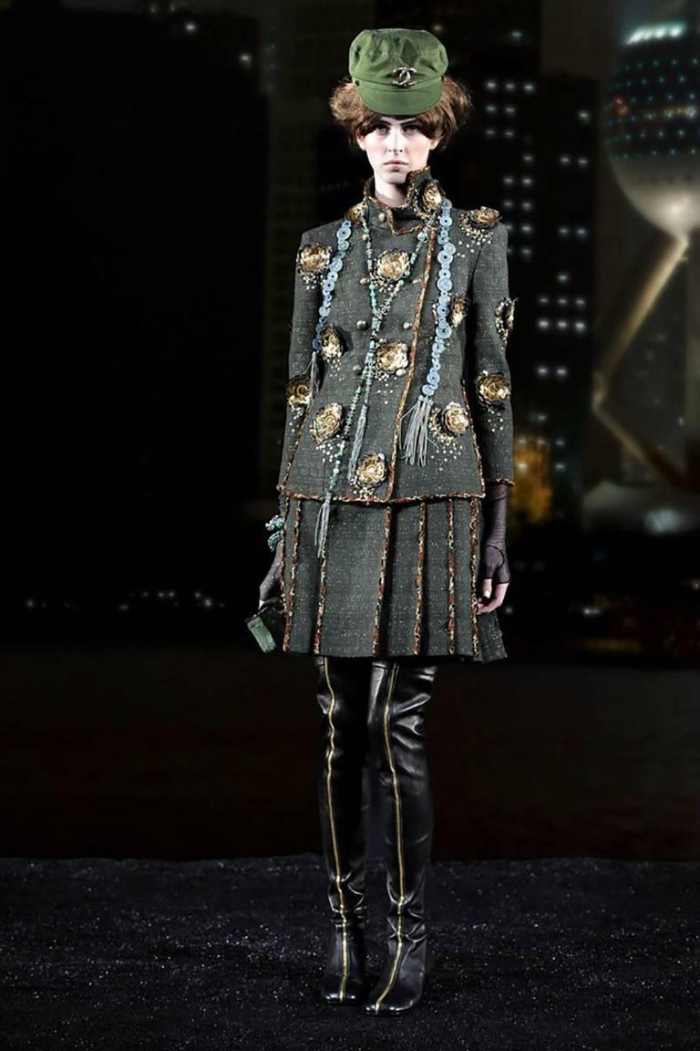 Chanel Pre-Fall 2010 Shanghai Runway Green skirt Suit with Gold Lesage Camelias.  Stand up collar, double row of olive enamelled buttons, lesage tweed trim, gold leather and sequin camelia detail, bracelet length sleeves, side slits at jacket sides.