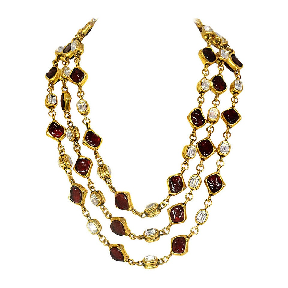 Chanel Vintage '80s Three Strand Red Gripoix & Strass Crystal Necklace Features three strands of alternating red gripoix and strass crystals set in goldtone metal.  Made in: France Year of Production: 1980s Stamp: CHANEL Closure: Hook and eye Color: