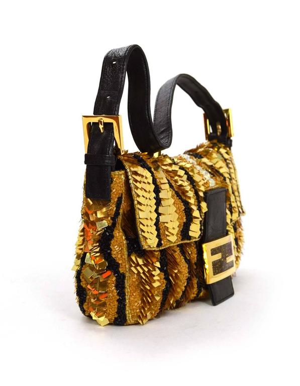 Fendi Gold & Black Sequin Baguette Features detachable black leather shoulder strap Made In: Italy Color: Gold and black Hardware: Goldtone Materials: Leather, beads and sequins Lining: Black satin Closure/Opening: Flap top with magnetic snap