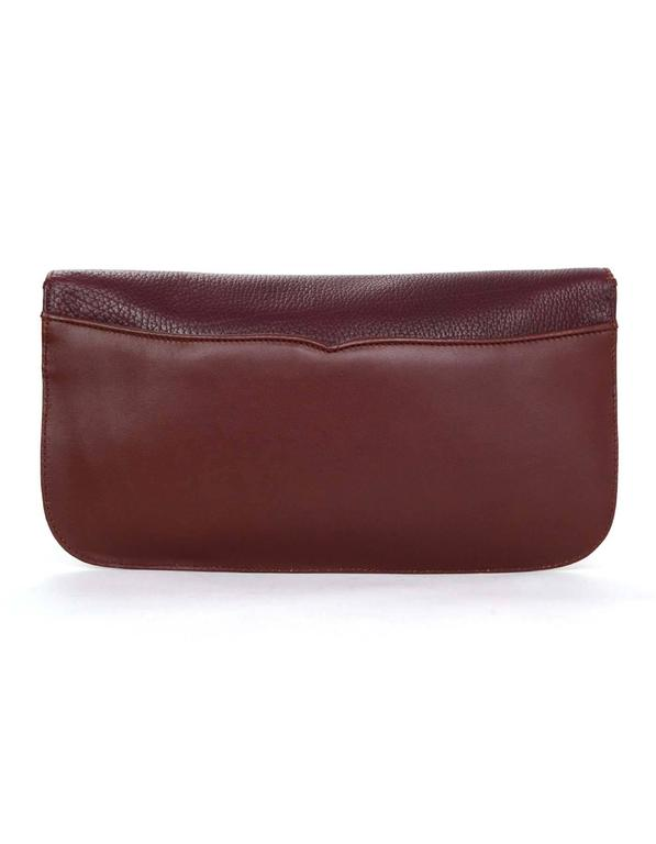 100% Authentic Cartier Burgundy Leather Clutch features textured and smooth leather with gold tone Cartier logo. Back slit pocket allows for extra space in addition to roomy interior.