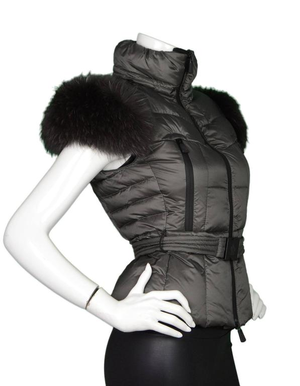 Moncler Dark Grey Down Vest Sz 0 NWT Features detachable raccoon fur at shoulders  Made In: Romania Color: Dark grey Composition: 64% Nylon, 36%  Polyurethane Lining: Black, 100% Nylon Filling: Down feathers Closure/Opening: Double zip up