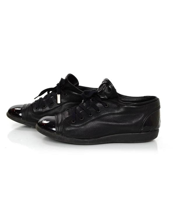 Chanel Black Leather Sneakers Features patent leather toe and heel cap  Made In: Italy Color: Black Materials: Leather and patent leather Closure/Opening: Lace up Sole Stamp: Chanel Made in Italy Overall Condition: Excellent pre-owned