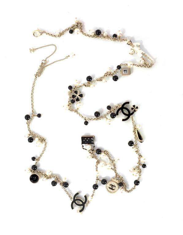 Chanel Pearl Beaded & Iconic Charm Necklace Features Chanel iconic charms throughout necklace Made In: Italy Year of Production: 2012 Color: Light gold, black, and ivory Materials: Faux pearl, beads, metal and enamel Closure: Lobster claw