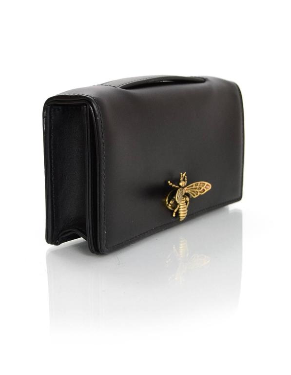 Christian Dior '17 Black Calfskin Bee Pochette Features small leather top handle  Made In: Italy Year of Production: 2017 Color: Black Hardware: Goldtone/Bronze Materials: Leather Lining: Black leather Closure/Opening: Flap top where back of bee