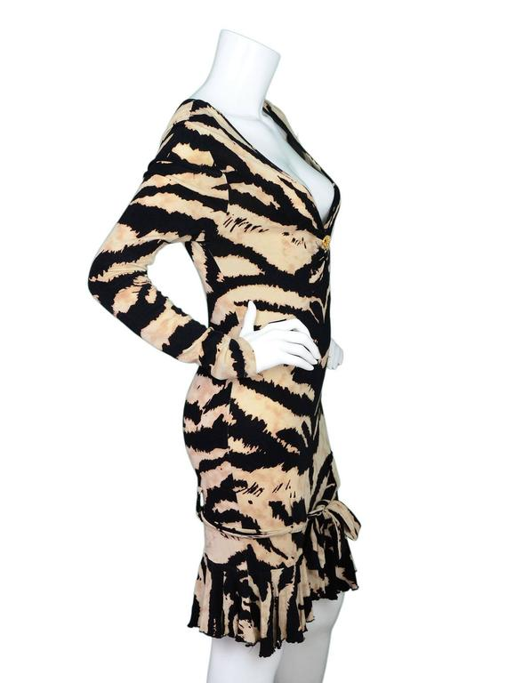 Roberto Cavalli Tiger Print Long Sleeve Dress  Features plunging neckline with goldtone and crystal serpent charm as well as ruffles at hemline  Made In: Italy Color: Black, brown and tan Composition: 94% viscose, 6% elastane Lining: