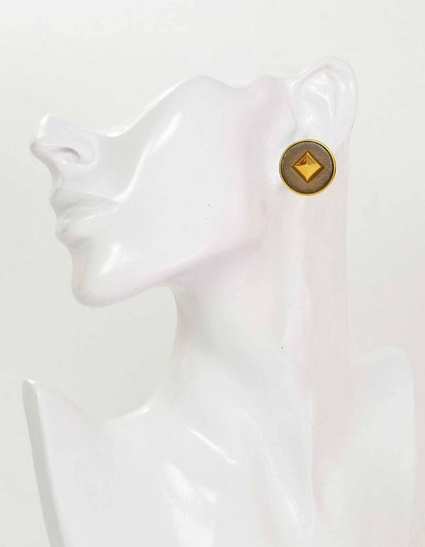 Hermes Gold & Taupe Leather Medor Clip On Earrings  Stamp: Hermes Paris Closure: Clip on Color: Taupe and goldtone Materials: Metal and leather Overall Condition: Excellent with the exception of some scratching to leather portion Includes: Hermes