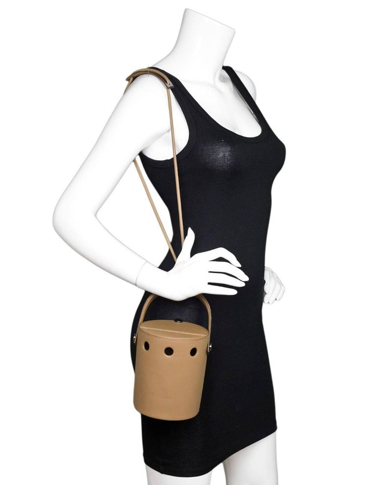 Perrin Taupe Calf Leather Le Mini Seau Structured Bucket Bag Features optional shoulder strap  Color: Taupe Materials: Leather, metal Lining: Taupe textile Closure/opening: Flap top Exterior Pockets: None Interior Pockets: None Retail Price: $1,295