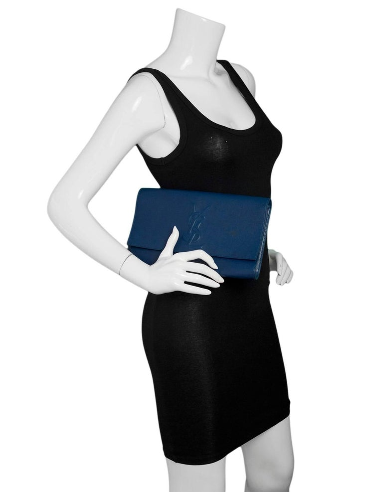 Yves Saint Laurent Blue Large Belle Du Jour Clutch  Made In: Italy Color: Blue Hardware: Leather Materials: Leather  Lining: Black textile Closure/Opening: Flap top with magnetic snap closure Exterior Pockets: None Interior Pockets: One small wall