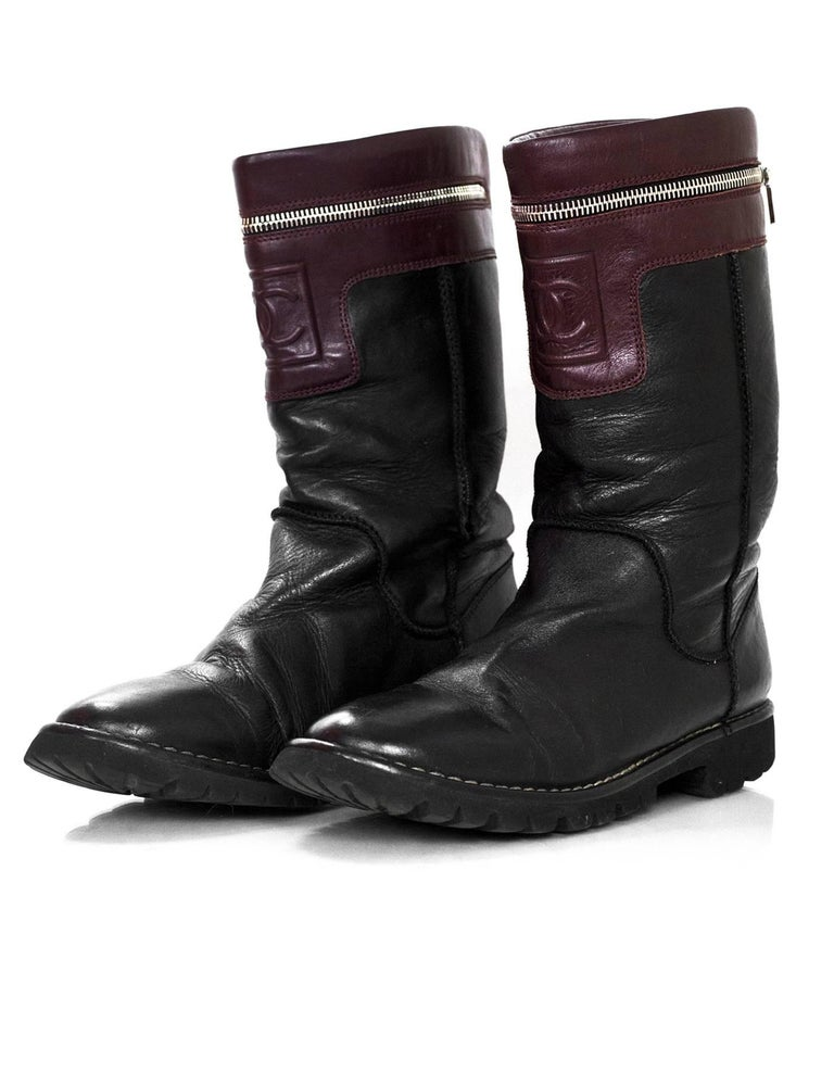 Chanel Black & Burgundy Calfskin Moto Zipper Boots Sz 40  Made In: Italy Color: Black, burgundy Materials: Leather Closure/Opening: Pull-up Sole Stamp: Chanel Made in Italy Retail Price: $1,195 + tax Overall Condition: Very good pre-owned condition