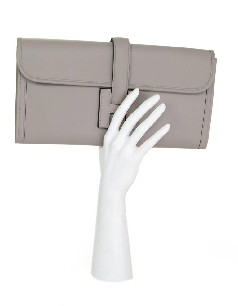 Hermes Grey Swift Leather Jige Elan 29 Clutch  Made In: France Year of Production: 2017 Color: Grey Hardware: None Materials: Swift leather Lining: Leather Closure/opening: Flap top with strap that goes through H Exterior Pockets: None Interior