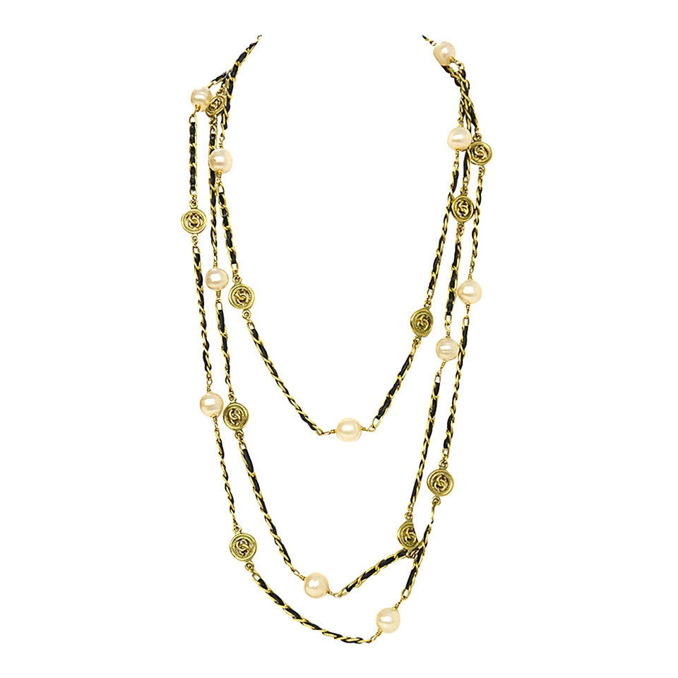 Chanel Vintage '94 Leather Woven Gold Chain Link Necklace Features CC Pendants and faux pearls throughout  Made in: France Year of Production: 1994 Stamp: 94 CC A Closure: None Color: Gold, black, and ivory Materials: Metal, leather and faux