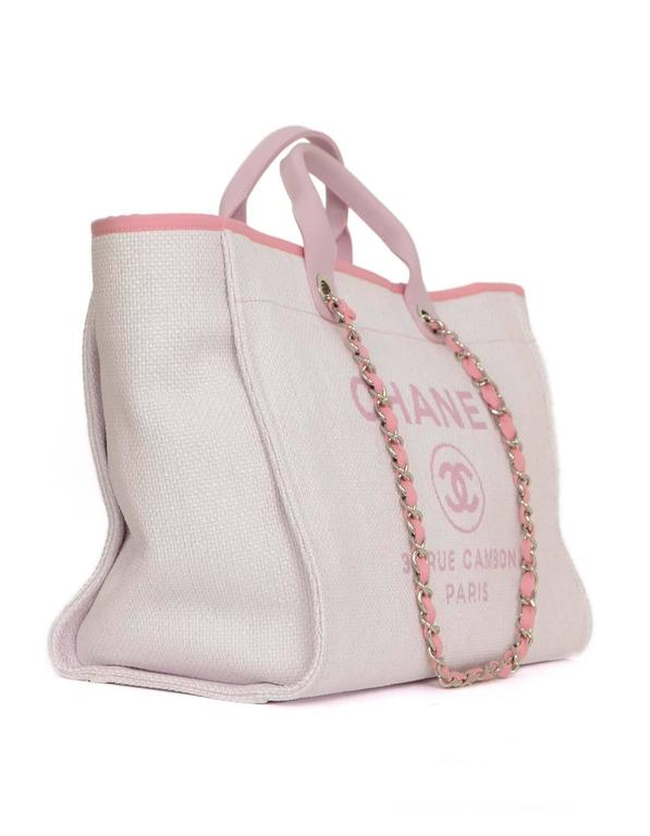 1c6100a11455 Chanel Pink Canvas Deauville Tote Features short pink leather handles and  longer chain link pink canvas