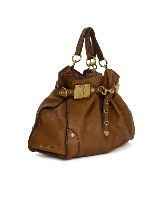 Miu Miu Tan Leather Belt Buckle Tote  Features gold hinges, grommets and buckles on both sides of bag for expanding and cinching Made In: Italy Color: Tan Hardware: Goldtone Materials: Leather Lining: Brown canvas Closure/Opening: Open top
