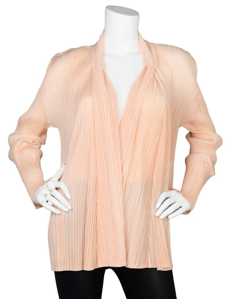 Pleats Please Peach Micro-Pleated Open Jacket Features jagged cut hemline  Made In: Japan Color: Peach Composition: 100% polyester Lining: None Closure/Opening: Open front Exterior Pockets: Two hip pockets Interior Pockets: None Overall Condition: