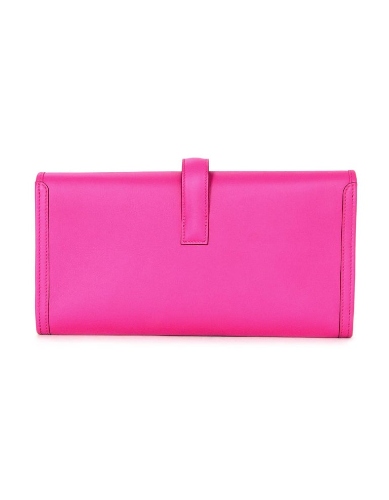 Hermes Magnolia Swift Leather Jige Elan 29 Clutch  Made In: France Year of Production: 2018 Color: Magnolia pink Hardware: None Materials: Swift leather Lining: Leather Closure/opening: Flap top with strap that goes through H Exterior Pockets: