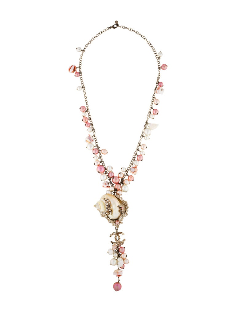 Chanel Pink & White MOP Shell Drop Necklace ​Features pink, peach and ivory faux pearls & shell chips Made In: France Year of Production: 2007 Color: Pink, ivory, peach and brass Materials: MOP shells, beads, faux pearls, rhinestones and