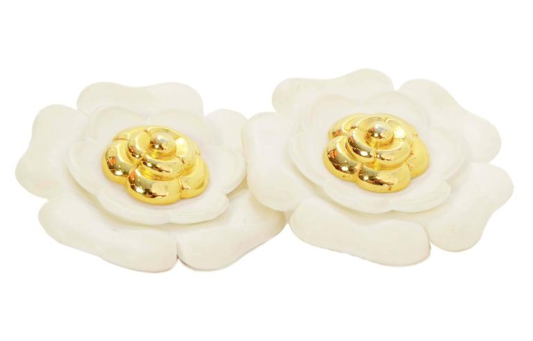 Chanel Vintage '60s Ivory & Gold Camelia Flower Clip On Earrings Features smaller goldtone flower in center of larger ivory flower Year of Production: 1950's-1960's Color: Ivory and goldtone Materials: Resin and metal Closure: Clip