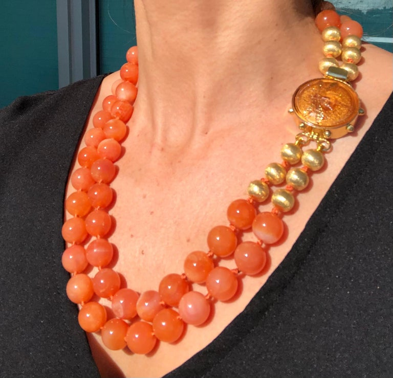 One-of-a-Kind What a hard to describe color! Is there such a thing as a creamy orange? At any rate, this 14mm double strand matinee length necklace is easy to wear with a rainbow of colors. The clasp is a perfect foil for the beads separated by six
