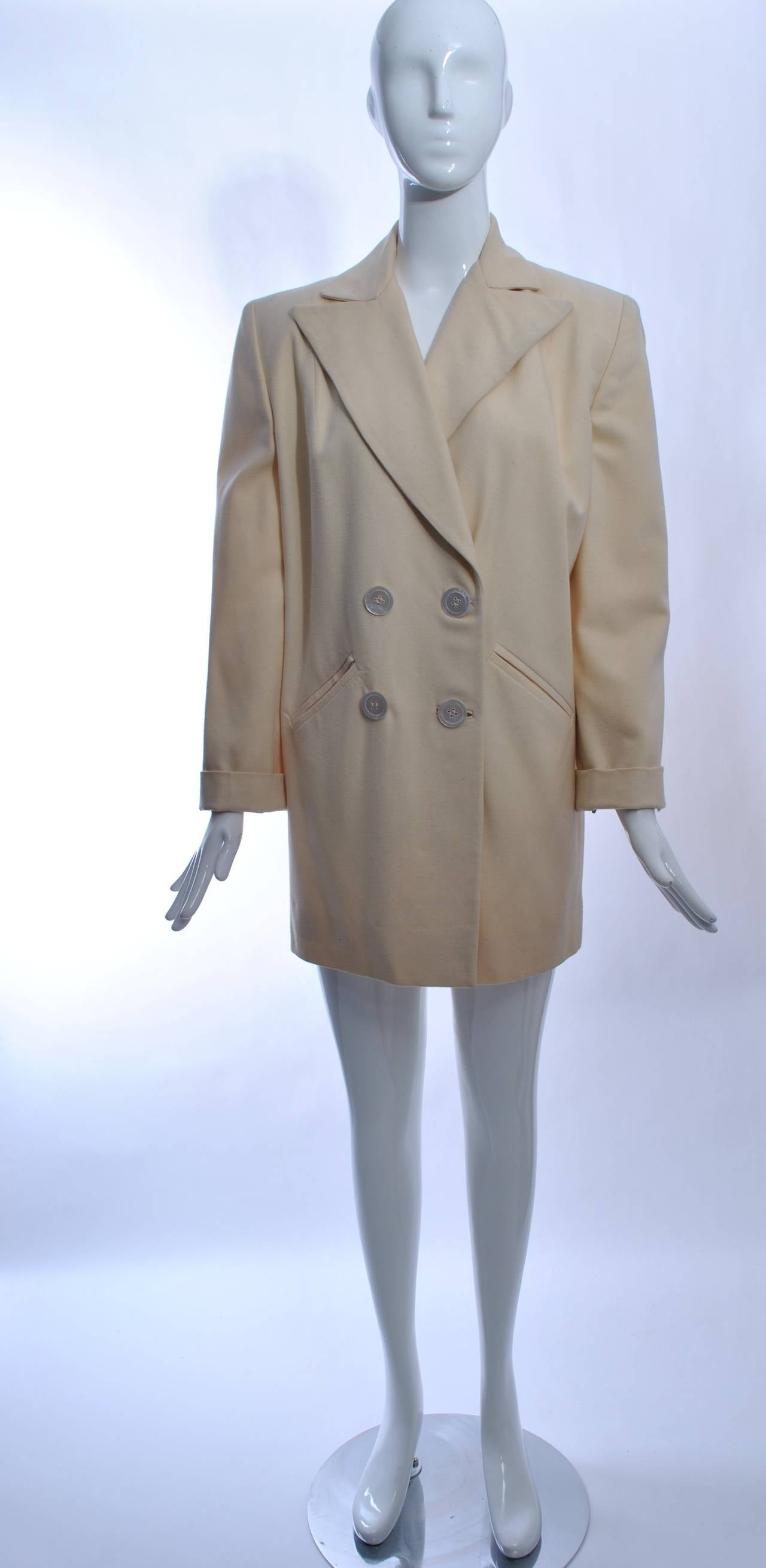 Chic 1940s style white wool blazer jacket with wide lapels, pearl double-breasted buttons and a wide back belt that pulls in the excess fabric in back. Other features include slanted, bound pockets, turn-back cuffs and squared shoulders.  Mid-thigh