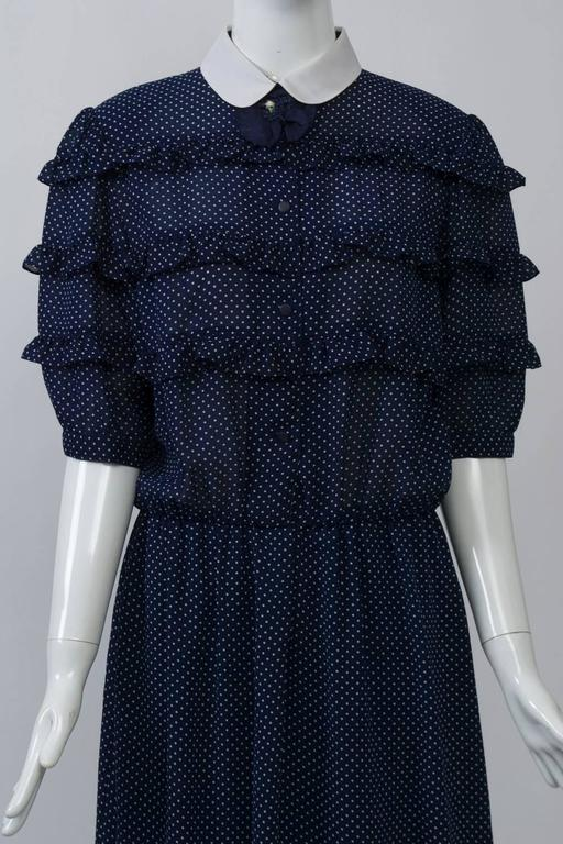 Hanae Mori modified shirtdress in a sheer and lightweight navy fabric with white micro dots features narrow rows of ruffles on the bodice and elbow-length sleeves, as well as a white peter pan collar. An elasticized waist creates a blouson style on