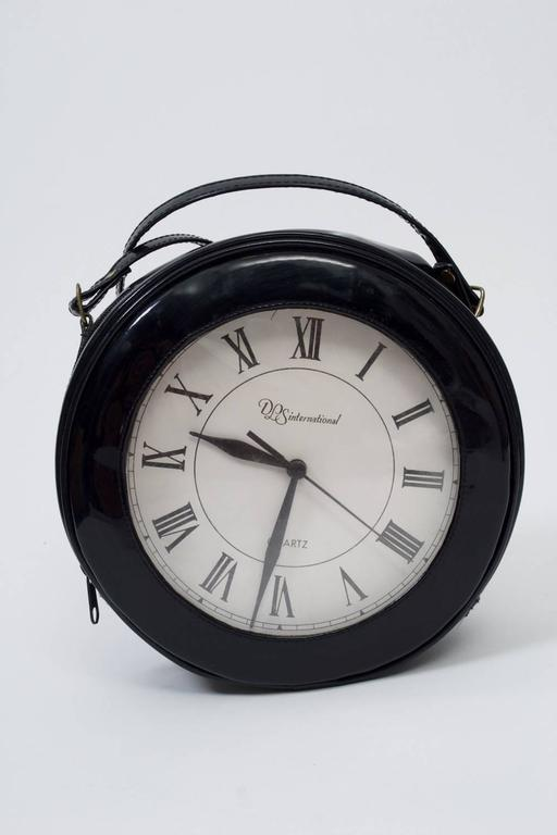 Black patent circular shoulder bag with roman-numeral clock face is a conversation piece. clock runs by battery and is housed in separate interior compartment. Top zipper.