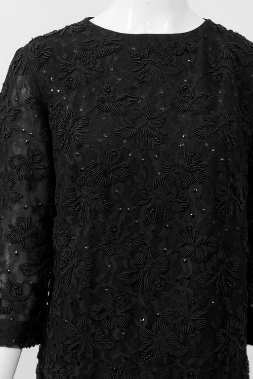 Classic and timeless cocktail dress in black lace with black floral beading throughout. Simple sheath styling with round neckline, three-quarter sleeves and  metal zipper in back. Dress lined, sleeves semi-sheer for a nice touch. Marked size 12, but