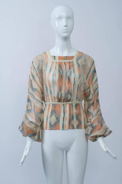 Koos van den Akker 1970s blouse in a sheer, native American-inspired print in shades of ivory, coral and turquoise. The blouse features a shallow square neckline, billowy sleeves with elastic wrists, an elastic waist, ivory and lace trim, buttons