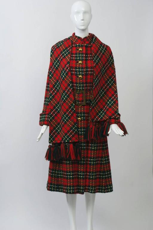 Wonderful red plaid coat featuring a wide belt, mandarin collar, and turn-back cuffs, accented with a fringed scarf. Fitted bodice, slight A-line skirt. Lined in green crepe. Excellent condition. Size S.
