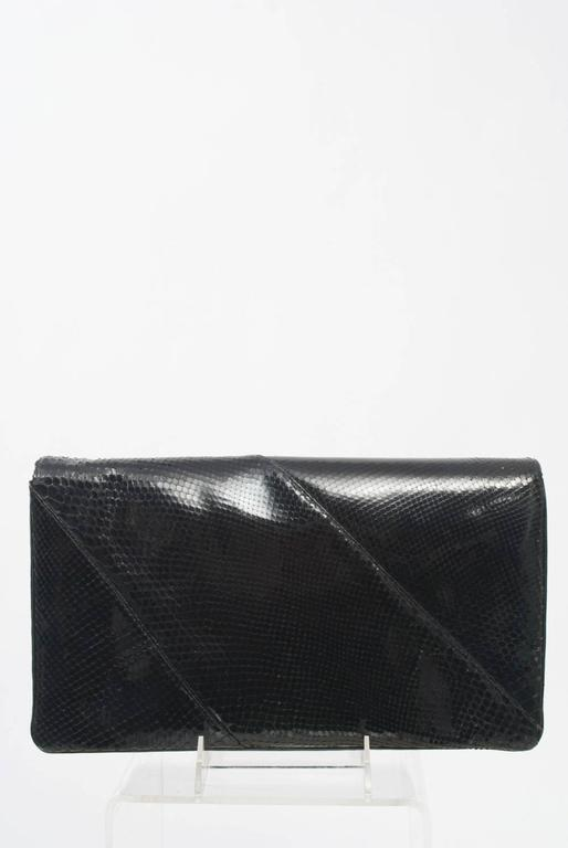 Nice size black snake clutch with silver metal trim featuring diagonally pieced skins and multiple interior compartments.