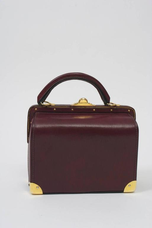 Impressive doctor's style satchel by Roberta di Camerino in a rich dark plum leather that has a striated texture. The structured handbag features unique hardware in polished gold metal, which include the slide-up and pull closures on the exterior