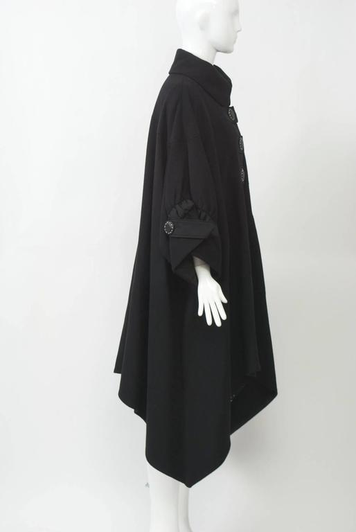 Kenzo swing coat with handkerchief hem in black cashmere with ribbon trim. The coat features a three grosgrain tabs with large buttons at front, a motif that is repeated at the wide, wrist-length cuffs, which are shirred and cut in. The rounded
