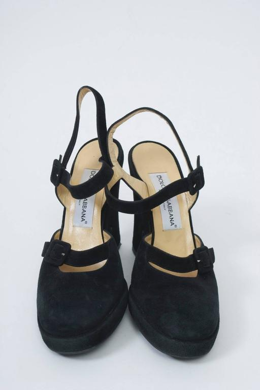 Black suede platform shoes with rounded toe and thick heel. Open back with ankle strap and buckle, which motif is repeated across the instep. Rubber sole.
