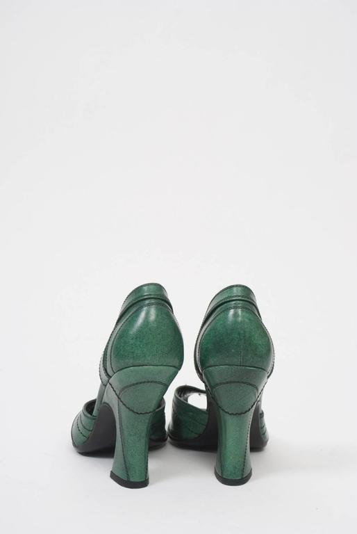 D'Orsay pumps in a soft shade of green leather from Prada feature peep toes, spool heels, and black decorative stitching throughout, as well as contoured slits on the sides of the heel backs. No signs of wear.