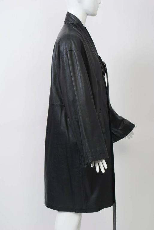 Kimono-style black leather coat by Jean Paul Gaulthier with dropped shoulders and wide sleeves. The collar band leads to two long ties to knot in front. Side pockets. Length is just above knees.