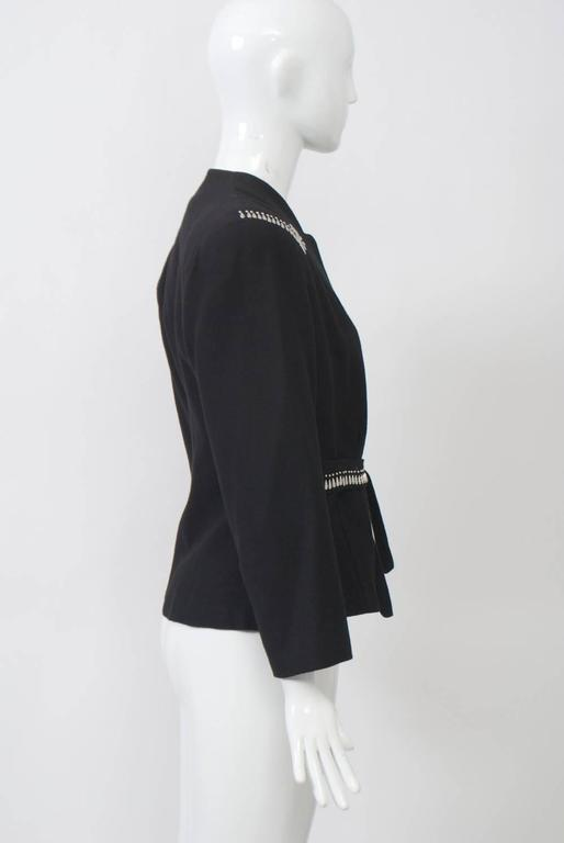 Black wool 1940s jacket with teardrop-shaped silver stud embellishment near shoulders and along front of self-tie waistband. Indented round neckline, square shoulders with pads, shaped body. Lined in black crepe.