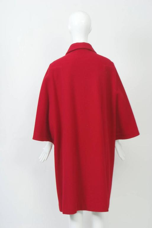 Striking red wool coat by Adolfo featuring cape sleeves, a small collar, and four black dome buttons down the front. Underneath the cape sleeves, the arms are free. Side pockets. Unlined. Interesting construction and detailing. Long black gloves